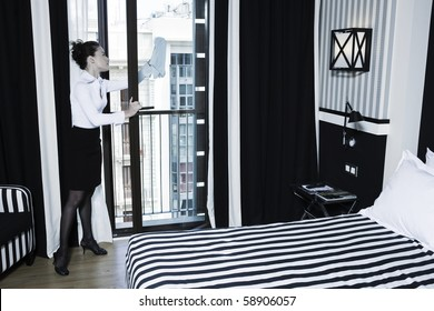 beautiful caucasian woman chambermaid cleaning window in a hotel bedroom
