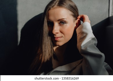 Beautiful Caucasian Woman Closeup Portrait Shot. Girl in White Shirt with Pensive Sight Touching her Hair Headshot Picture Front View. Attractive Lady with Nude Makeup Looking at Camera