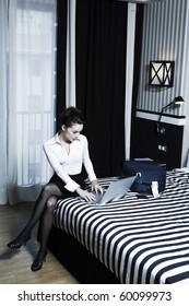 beautiful caucasian woman computing in a hotel bedroom