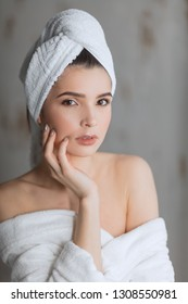 Beautiful caucasian woman with dark eyes and healthy white skin, dressed in bathrobe with naked shoulders and towel on head, nude makeup, beauty cosmetic salon atmosphere and facial spa treatment.