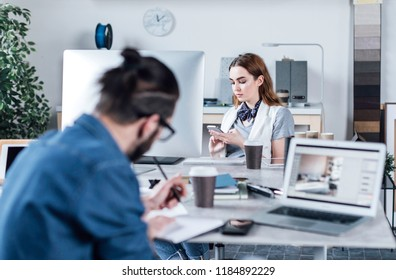 Beautiful Caucasian woman designer sitting at office and typing on her cell phone.