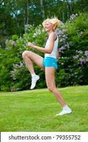 Beautiful caucasian woman doing pilates exercises in the park