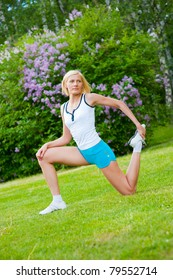 Beautiful caucasian woman doing stretching exercises in the park