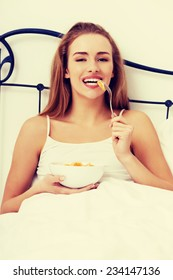 Beautiful caucasian woman eating fresh fruit for breakfast in bed.