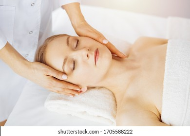 Beautiful caucasian woman enjoying facial massage with closed eyes in sunny spa salon. Relaxing treatment in medicine and Beauty concept