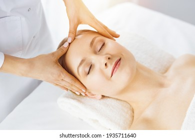 Beautiful caucasian woman enjoying facial massage with closed eyes in sunny spa salon. Relaxing treatment in medicine