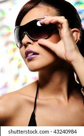 Beautiful caucasian woman in the fashion sunglasses touching it
