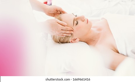 Beautiful caucasian woman having a facial massage treatment in spa salon with the hands of a therapist as a foreground, selective focus, concept spa and beauty, facial spa treatment, esthetic spa.