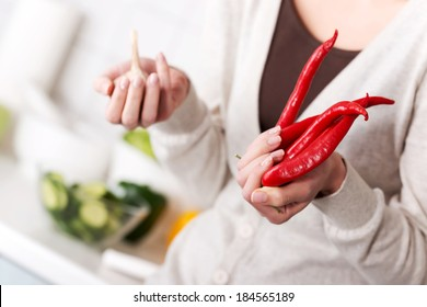 Beautiful caucasian woman is holding chili peppers and garlic. Kitchen background.