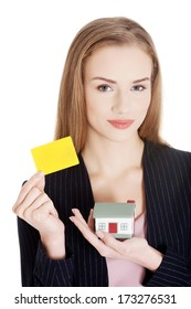 Beautiful caucasian woman is holding empty personal card and house model. Isolated on white.