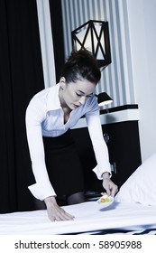 beautiful caucasian woman housekeeper doing bed in a hotel bedroom