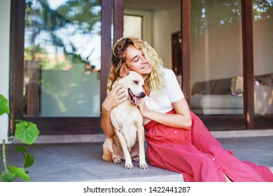 Beautiful caucasian woman hugging her mongrel dog pet in front of her house