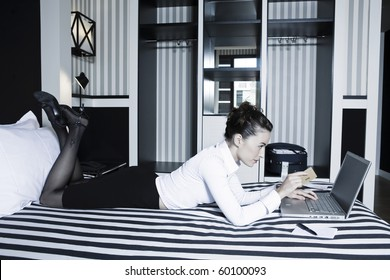 beautiful caucasian woman internet payment hold credit card in a hotel bedroom