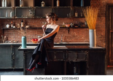 Beautiful caucasian woman in the kitchen with modern loft interior drinking champagne.
