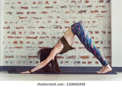 beautiful caucasian woman with long hair and slender body doing yoga in yoga class, adho mukha svanasana yoga pose