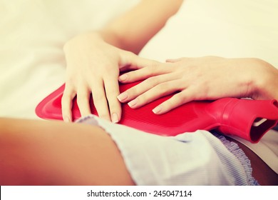 Beautiful caucasian woman lying in bed with hot water bag.