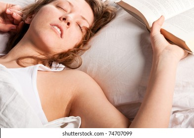 beautiful caucasian woman is lying in bed at morning and holding open book