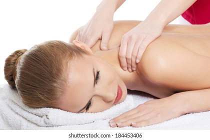 Beautiful caucasian woman lying on the massage table and is being massaged. Over white background.