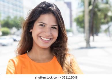 Beautiful caucasian woman in a orange shirt in the city