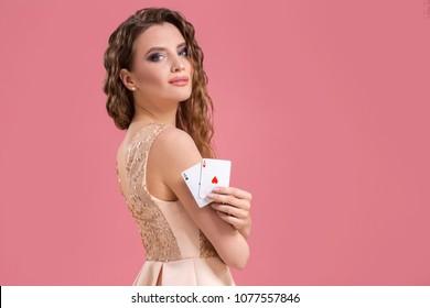 Beautiful caucasian woman with poker cards gambling in casino. Studio shot