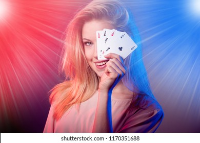 Beautiful caucasian woman with poker cards gambling in casino with light rays shining over her
