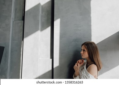 Beautiful Caucasian Woman Portrait Wall Copy Space. Light Brown Hair Girl Wear White Shirt Head and Shoulder Picture. Calm Peaceful Elegant Lady with Makeup. Shadow on Grey Minimal Background