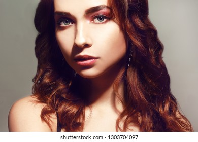 Beautiful caucasian woman with short brown curly hair. Portrait of a pretty young adult girl. Sexy face of an attractive lady posing at studio over grey background. Woman with pink natural make up.