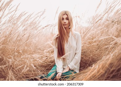 Beautiful  caucasian woman sitting on the grass on summer