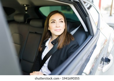Beautiful caucasian woman smiling while looking outside the car window. Businesswoman arriving at her office building in a taxi cab of a ride-share app