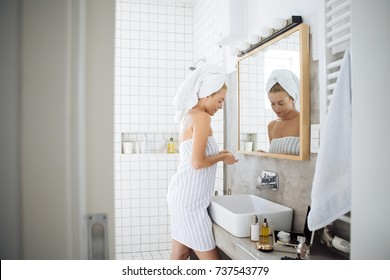 Beautiful Caucasian woman in towels standing in bathroom after shower.