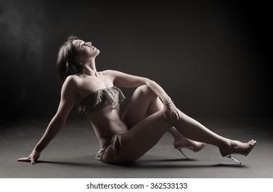 beautiful, caucasian woman wearing a bikini posing in studio
