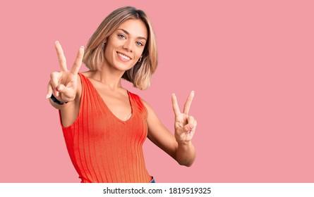 Hermosa mujer caucásica con ropa casual sonriendo mirando a la cámara mostrando los dedos haciendo señal de victoria. número dos.