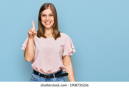 Beautiful caucasian woman wearing casual clothes showing and pointing up with finger number one while smiling confident and happy.