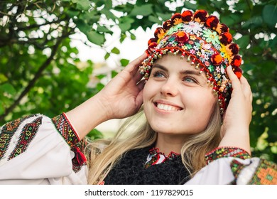 Beautiful caucasian woman wearing ethnic and traditional of the Carpathian mountain Ukrainian clothes. Village background in the autumn.