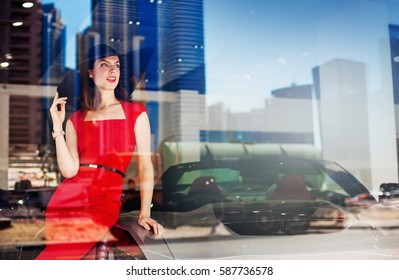beautiful caucasian woman wearing red dress with a luxury car