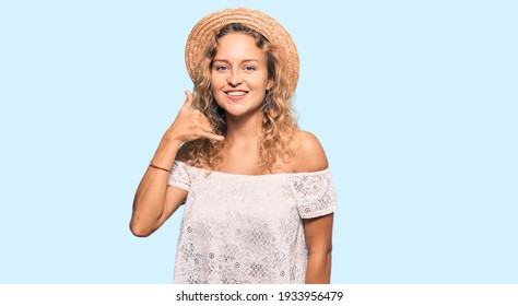 Beautiful caucasian woman wearing summer hat smiling doing phone gesture with hand and fingers like talking on the telephone. communicating concepts.