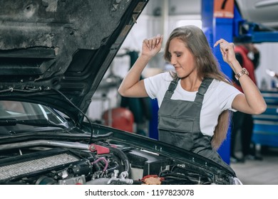 Beautiful caucasian woman wearing sunglases, white t-shirt and black jumpsuit, having a problem with black car. Upset woman emotionally reacting on broken car.