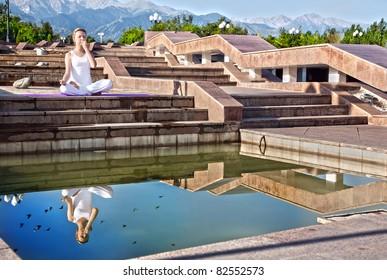 Beautiful Caucasian woman in white cloth doing nadi suddhi pranayama with Pranav mudra in ardha padmasana, half lotus pose. Woman Sitting on the  stairs near the water with her reflection at Mountain
