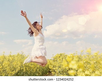 Beautiful caucasian woman in white dress jumping up with raised hands outdoor. Field with yellow flowers around