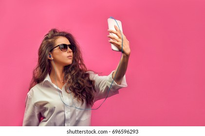 Beautiful caucasian woman in a white shirt  in glasses with headphones, holding a white tablet in hands and makes selfie photo on a pink bright  background. Studio photo with a stylish model.