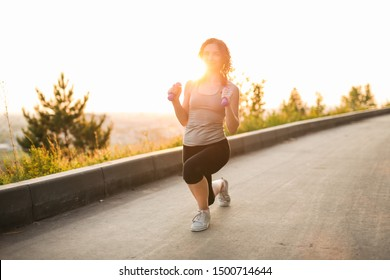 beautiful caucasian young brunette girl goes in for sports in the park, evening jogging and sports exercises outdoors in the city. Healthy lifestyle concept