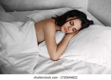 beautiful Caucasian young brunette girl sleeping in the morning on a pillow under a white blanket on the bed