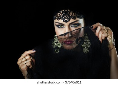 Beautiful caucasian young woman with black veil on face, fency arabian costume