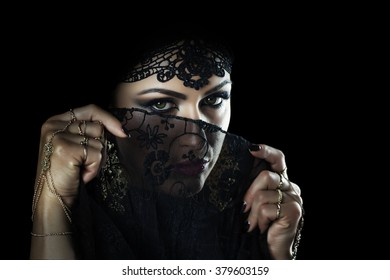 Beautiful caucasian young woman with black veil on face, fancy arabian costume