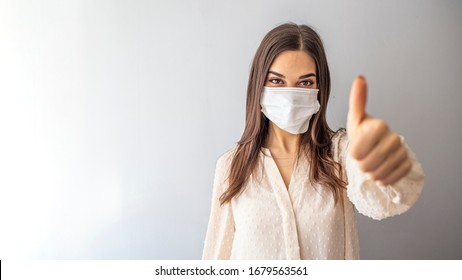 Beautiful caucasian young woman with disposable face mask. Protection versus viruses and infection. Studio portrait, concept with white background. Woman showing thumb up.