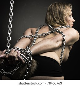Beautiful chained and nude girl bent away from the camera, looking away