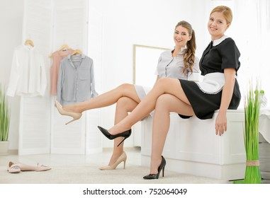 Beautiful chambermaids trying on shoes in room