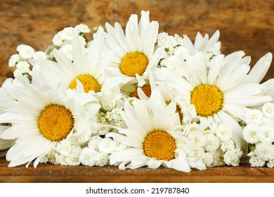 Beautiful chamomiles on wooden background