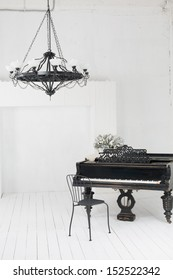 A beautiful chandelier and a piano in the room with white floors and walls