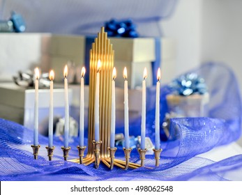 Beautiful Chanukah decorations in blue and silver with gifts and dreidels and a Chanukiah with nine Chanukah candles for the Jewish holiday Hanukkah with copy space.